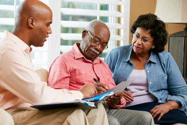 Agent helping senior couple with paperwork